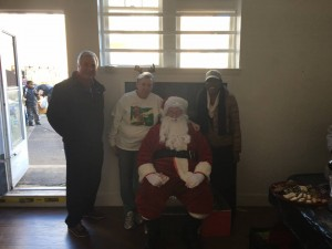 Mayor Moor, Asbury Park Toy Drive's Connie Breech and Councilwoman Yvonne Clayton join Santa for holiday giveaway